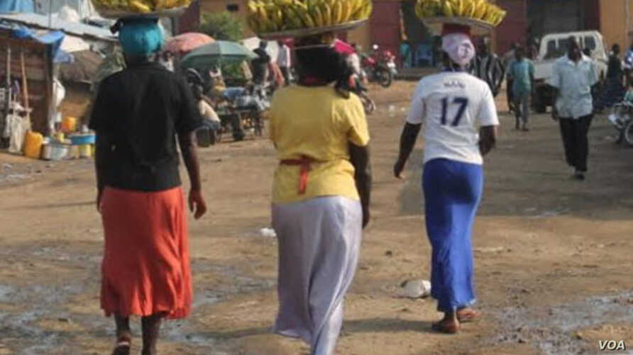 Farhida Hussein (No. 17 T-shirt on right) carries bananas into a market in Juba. The 33-year-old mother of three doesn't put the 15-20 South Sudanese pounds she makes a day by selling the bananas in a bank because she thinks she earns too little to o