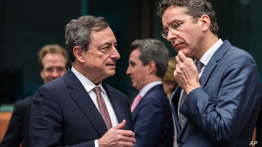 Dutch Finance Minister Jeroen Dijsselbloem, right, talks with European Central Bank Governor Mario Draghi during a meeting of eurogroup finance ministers at the European Council building in Brussels, March 9, 2015.
