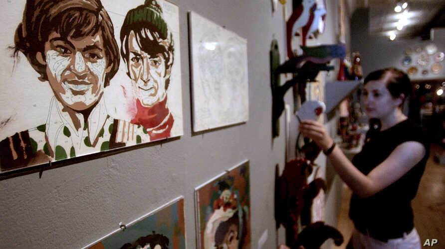 Kate Lawroski looks at a display of paint-by-numbers artwork of the Monkeys musical group Thursday, July 1, 2004, at Chicago's Intuit gallery.