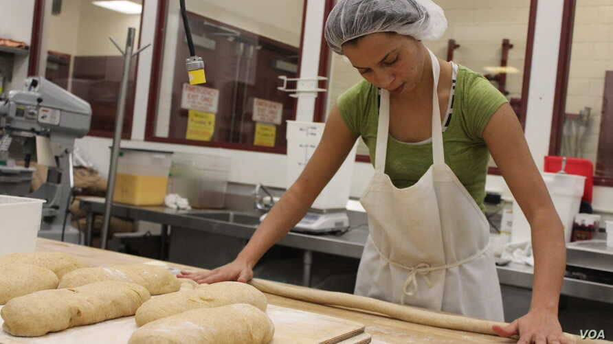 Morocco native Fatiha Outabount, 27, shapes dough at the Hot Bread Kitchen bakery in New York. (VOA-D. Grunebaum)