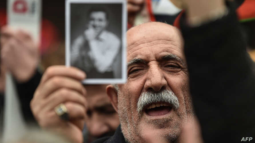 A man holds a picture of Selahattin Demirtas as people gather outside Bakirkoy courthouse in Istanbul, Jan. 12, 2018, in support of the jailed co-chair of the People's Democratic Party (HDP).