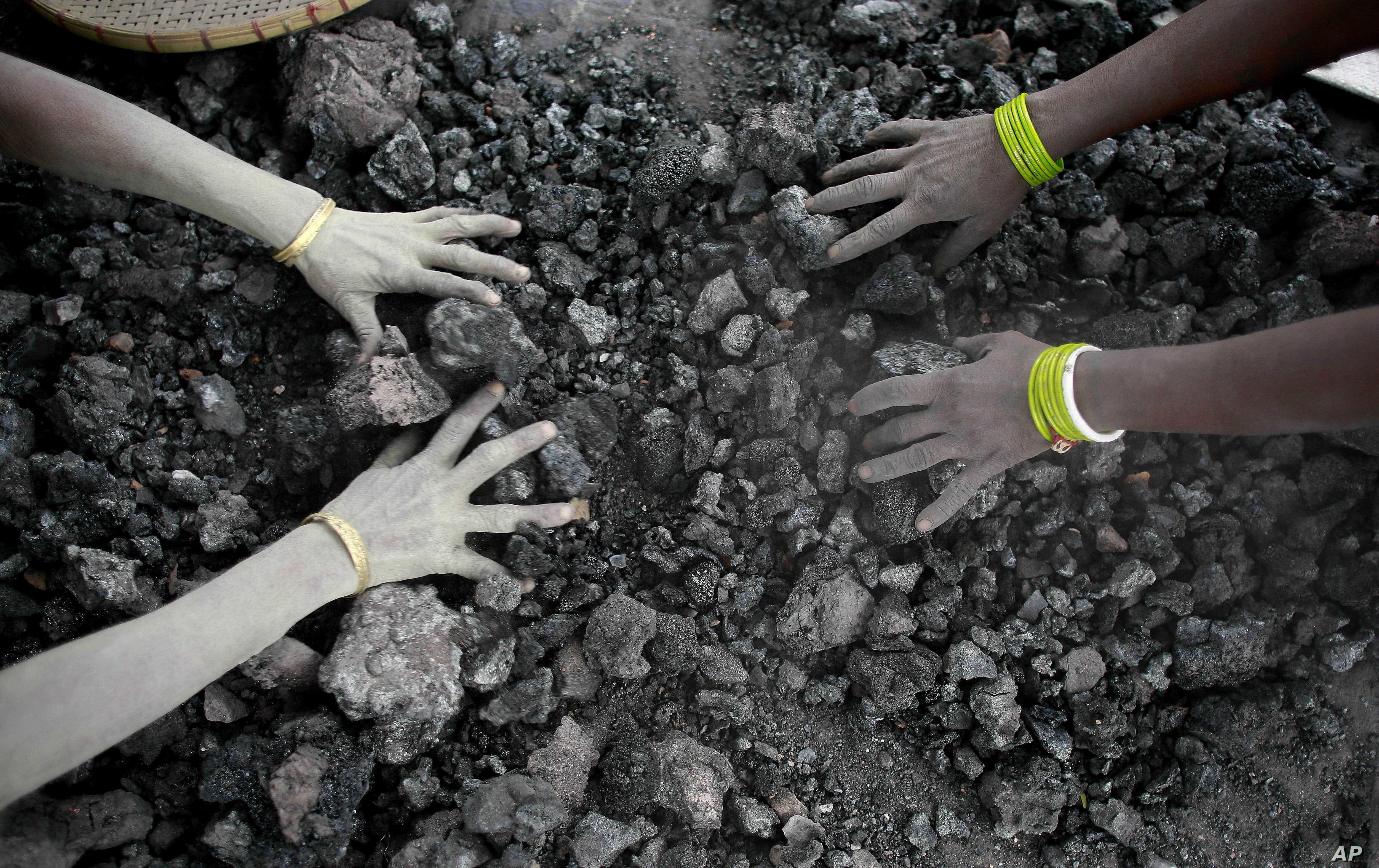 FILE - In this Monday, Dec. 14, 2015, file photo, Indian women use bare hands to pick reusable pieces from heaps of used coal discarded by a carbon factory in Gauhati, India. Thirteen young miners were missing and feared dead following the collapse o