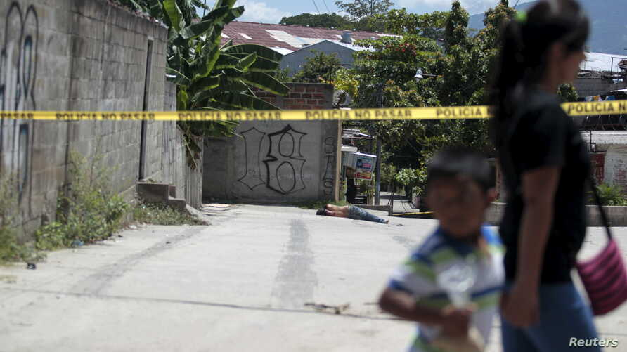A woman and a child walk past a crime scene where the body of a dead man was found after he was shot by alleged gang members in the El Castillo neighborhood in Soyapango, on the outskirts of San Salvador, El Salvador, July 20, 2015.
