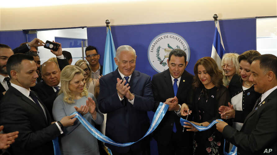 Israeli Prime Minister Benjamin Netanyahu, third left, his wife, Sara, second left, and Guatemalan President Jimmy Morales, center, watch as the Guatemalan first lady Hilda Patricia Marroquin cuts the ribbon during the dedication ceremony of the emba