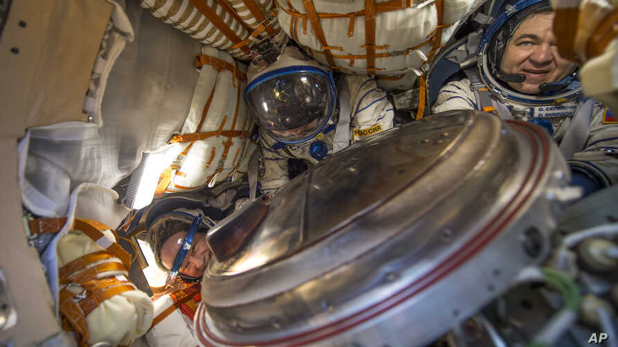 This photo provided by NASA shows NASA astronaut Jeff Williams, left, Russian cosmonaut Alexey Ovchinin of Roscosmos, center, and Russian cosmonaut Oleg Skripochka of Roscosmos inside the Soyuz TMA-20M spacecraft a few moments after they landed in a