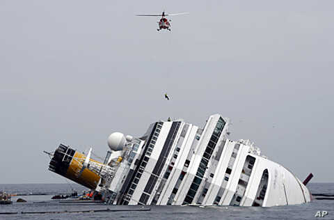 An Italian firefighter is lowered from a helicopter onto the grounded cruise ship Costa Concordia off the Tuscan island of Giglio, Italy, January 31, 2012.