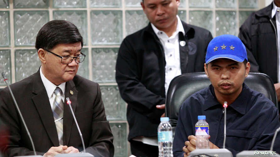 Jerry Umlang (R) answers questions from the members of the media regarding his alleged involvement in the kidnapping and murder of South Korean businessman Jee Ick-Joo while Department of Justice Secretary Vitaliano Aguirre (L) looks on during a pres