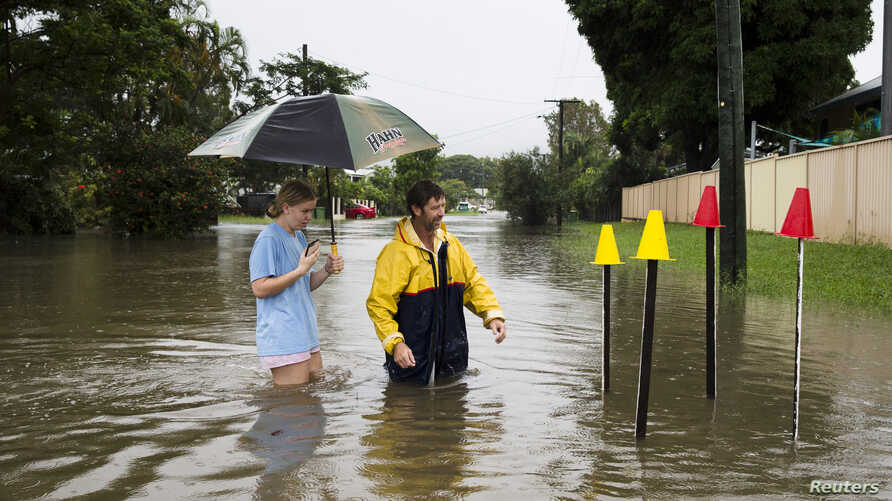 Resident Paul Shafer and his daughter Lily stand in floodwaters near star pickets that show where the storm water cover has been removed in Hermit Park, Townsville, northern Queensland, Australia, Feb. 2, 2019.