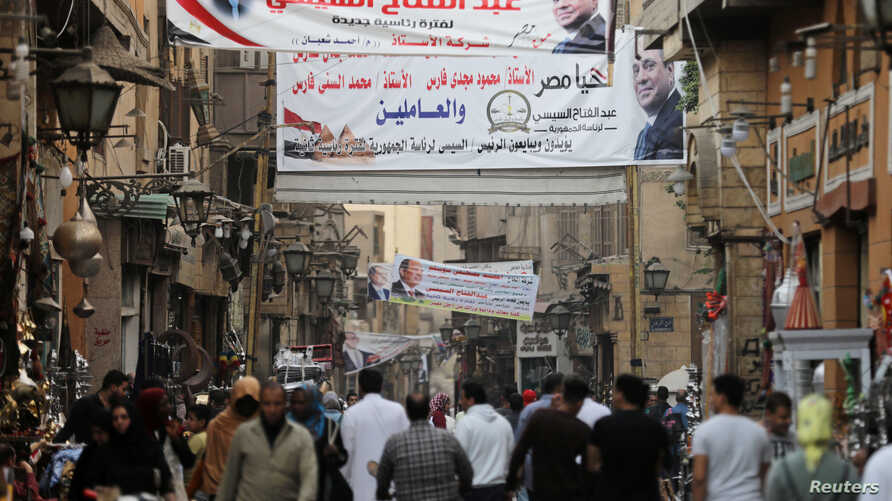 People walk under posters of Egyptian President Abdel Fattah al-Sisi for the upcoming presidential election, in Cairo, March 19, 2018.