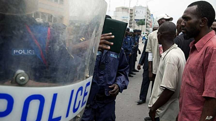 Opposition supporters and anti riot policemen face-off in front of the post office in Kinshasa, October 13, 2011.