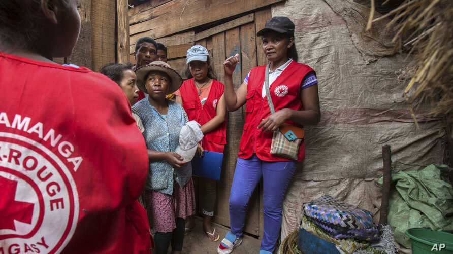 Red Cross volunteers talk to villagers about the plague outbreak, 30 miles west of Antananarivo, Madagascar, Oct. 16, 2017.