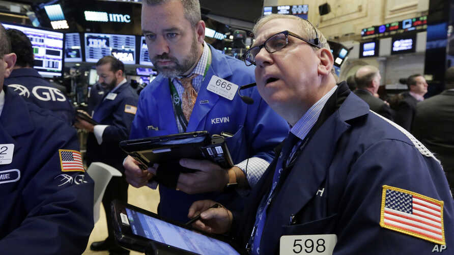 FILE - Traders Kevin Lodewick, left, and Richard Cohen work on the floor of the New York Stock Exchange, Sept. 26, 2016.