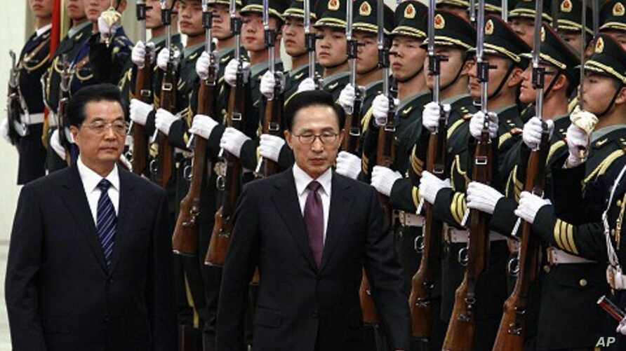 South Korean President Lee Myung-bak (2nd L) walks with Chinese President Hu Jintao (L) as they inspect a guard of honor during an official welcoming ceremony in the Great Hall of the People in Beijing January 9, 2012.