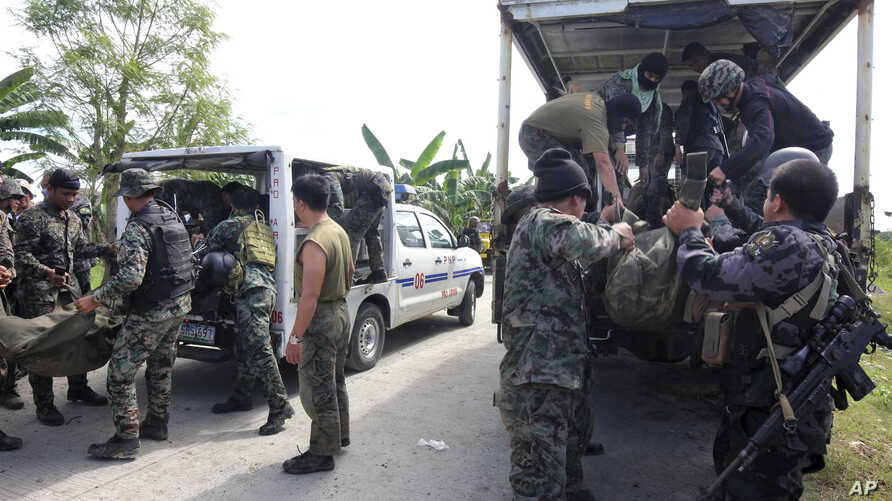Members of the Philippine National Police Special Action Forces load bodies of police commandos into vehicles in Maguindanao, Philippines, Jan. 26, 2015.