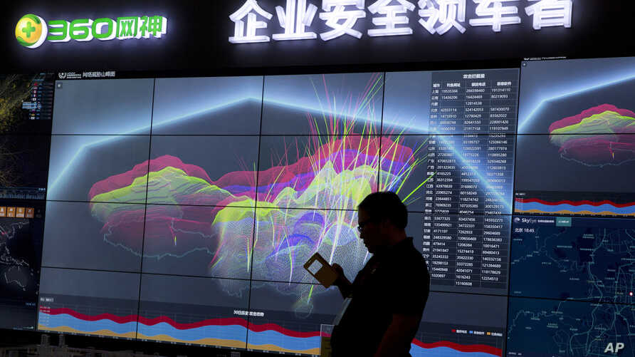 A worker is silhouetted against a computer display showing a live visualization of the online phishing and fraudulent phone calls across China during the 4th China Internet Security Conference (ISC) in Beijing, Aug. 16, 2016.