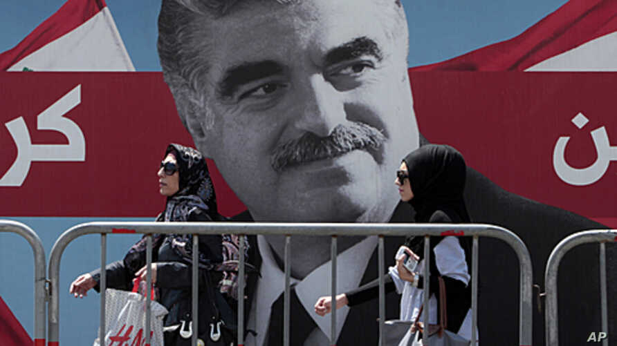 Lebanese women pass by a giant portrait of slain Lebanese Prime Minister Rafik Hariri near his grave, in downtown Beirut, June 30, 2011