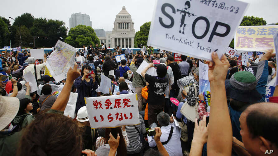 Protesters hold anti-war placards in front of the National Diet building during a rally in Tokyo, Sunday, Aug. 30, 2015. Thousands of Japanese protested outside the parliament a set of security bills designed to expand the role the country's military
