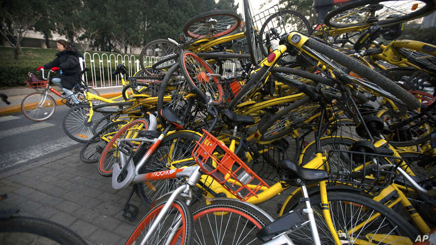 FILE - A woman rides a bicycle past Mobike and Ofo branded shared bicycles piled on a traffic median in Beijing, Tuesday, Nov. 21, 2017.