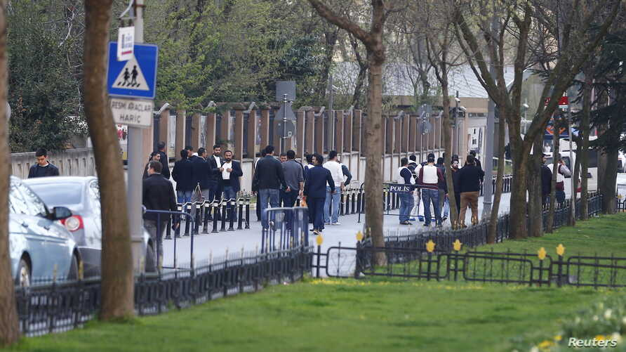 Police officers stand guard outside Istanbul's police headquarters after two people attacked the site, April 1, 2015.