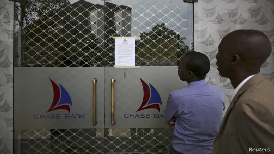 People read a notice from the Central Bank of Kenya taped to the closed entrance of a Chase Bank branch, after the bank was put under receivership, in Nairobi, Kenya, April 8, 2016.