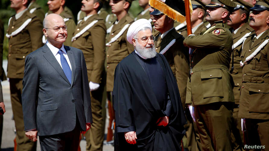 Iraq's President Barham Salih walks with Iranian President Hassan Rouhani during a welcome ceremony at Salam Palace in Baghdad, Iraq, March 11, 2019.