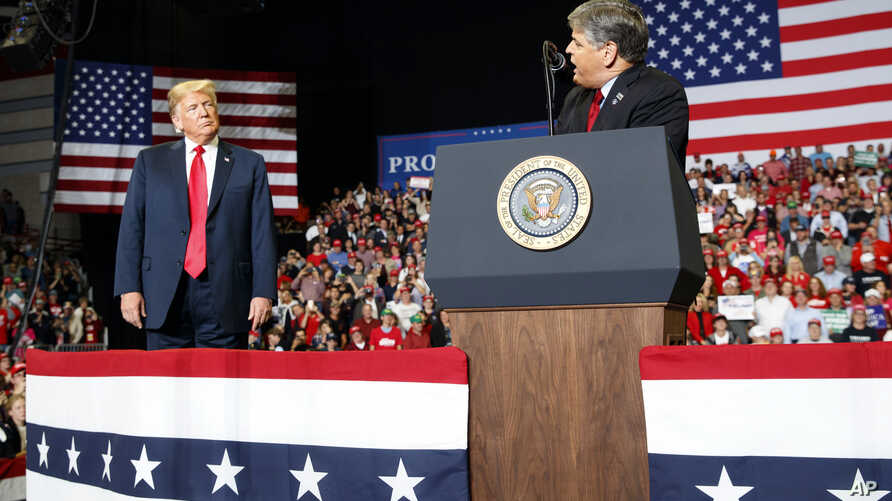 President Donald Trump listens Fox News' Sean Hannity speak during a rally at Show Me Center in Cape Girardeau, Mo., Nov. 5, 2018.