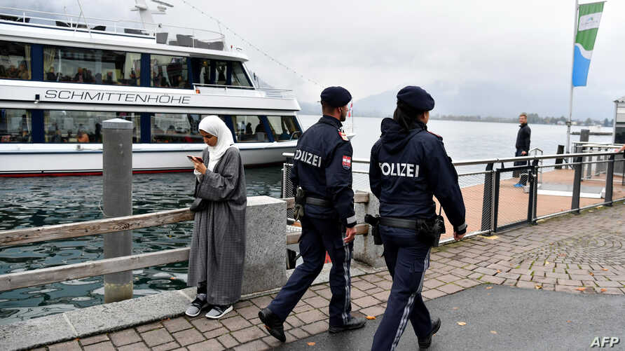 Police officers patrol as they pass by a woman wearing a traditional hijab headdress in Zell am See, Austria, Oct. 1, 2017.