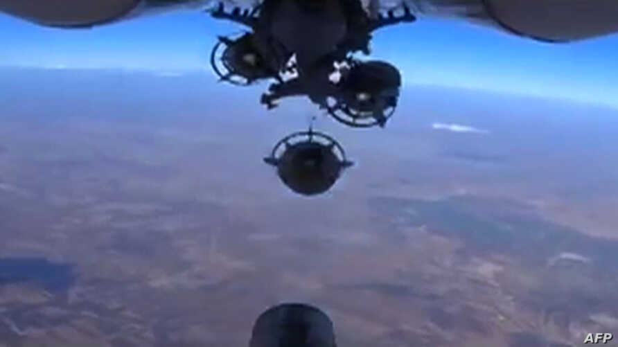 An image grab made from a video released Oct. 5, 2015, by the Russian Defense Ministry reportedly shows a Russian aircraft dropping bombs during an airstrike against Islamic State group's positions at an undisclosed location in Syria.