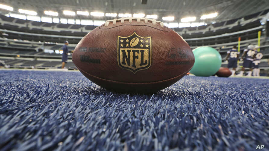 A football rests on the colored turf during an NFL football minicamp at the Dallas Cowboys' stadium, June 19, 2014, in Arlington, Texas.