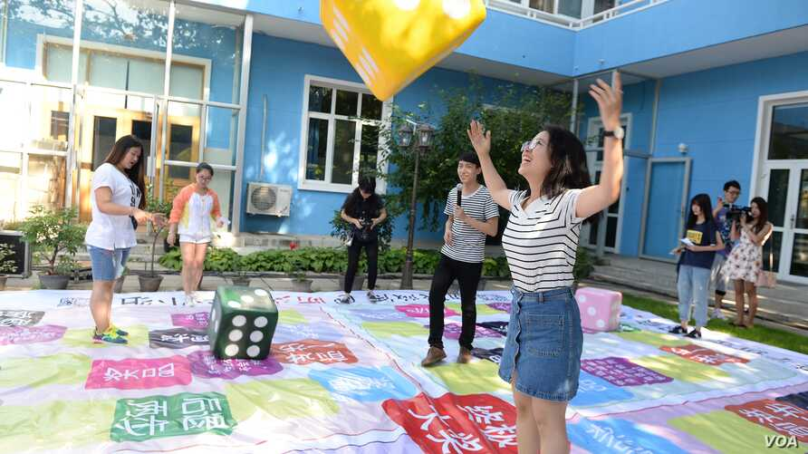 """Young people play an """"HIV knowledge"""" board game at an event to promote sexual and reproductive health among adolescents supported by the China Center for Health Education and UNICEF China."""