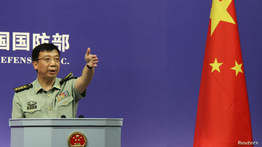FILE - Spokesman of China's Defense Ministry Geng Yansheng gestures to a journalist after his speech during a news conference in Beijing.