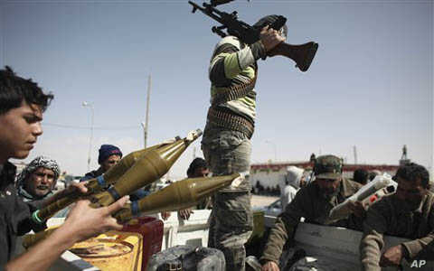 Defected Libyan soldiers and volunteers load weapons onto a truck on the outskirts of the eastern town of Brega, Libya, Thursday, March 3, 2011. Mutinous army units in pickup trucks armed with machine-guns and rocket launchers deployed around the str