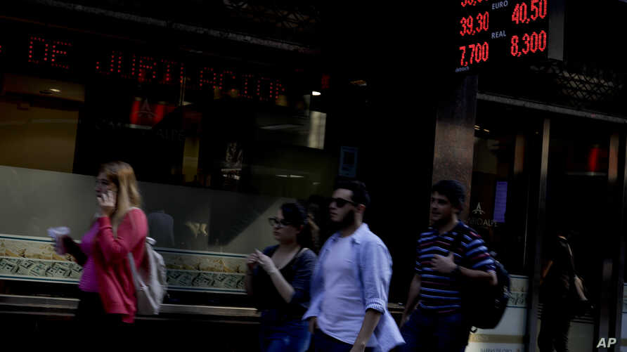 People walk by a currency exchange office in Buenos Aires, Argentina, Aug. 29, 2018.