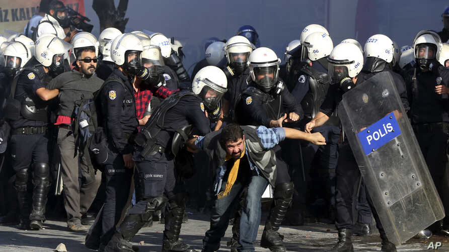 Turkish riot police detain protesters rallying against what they see as Turkey's inaction against Islamic State militants moving against Kurds in Syria, close to Turkey's border, in Ankara, Oct. 7, 2014.