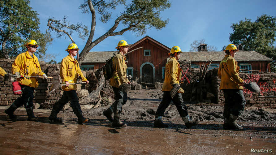 Rescue workers enter properties to look for missing persons after a mudslide in Montecito, California, Jan. 12, 2018.