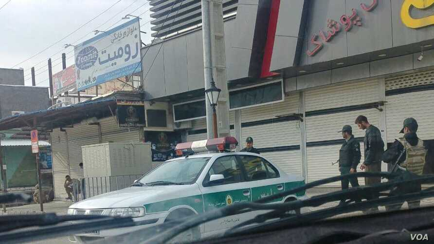In this photo taken by a Baneh resident, Iranian security forces, including an IRGC officer armed with an Uzi, far right, stage a show of force in Baneh, Iran, as a general strike continues, May 2, 2018.