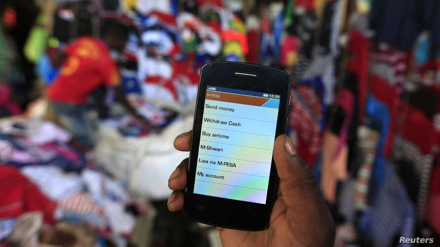 A man holds up his mobile phone showing an M-Pesa mobile money transaction page at an open-air market in Kibera in Kenya's capital, Nairobi, Dec. 31, 2014.