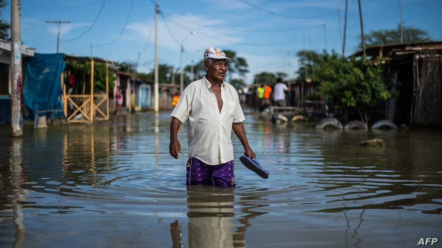 """A local resident wades through water on a street in the """"El Indio"""" settlement on the outskirts of Piura, in northern Peru."""