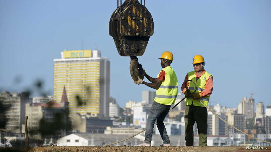 FILE - Construction workers build a new bridge against the skyline of Mozambique's capital Maputo, April 15, 2016.