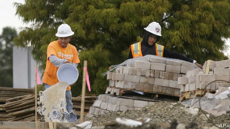 FILE - Workers bucket water from a waterlogged construction site in the Dallas suburb of Richardson, Texas, Oct. 26, 2015. As the flooding from Hurricane Harvey recedes, the rebuilding of Houston may be slowed by a lack of immigrant labor.