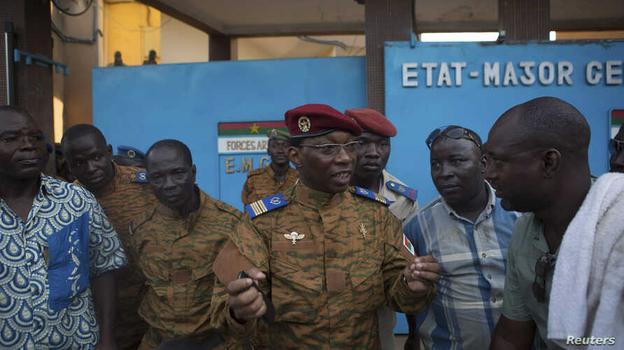 An army spokesman speaks to anti-government protesters outside military headquarters in Ouagadougou, capital of Burkina Faso, Oct. 30, 2014.