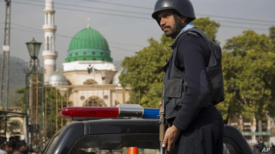 FILE - A Pakistani police officer stands guard outside the Barri Imam shrine, as security is beefed up in the capital following a suicide attack at a Sufi shrine in interior Sindh, Islamabad, Pakistan.