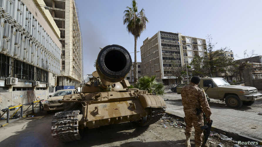 A member of the Libyan pro-government forces, backed by locals, stands near a tank in Benghazi, Libya, Jan. 21, 2015.