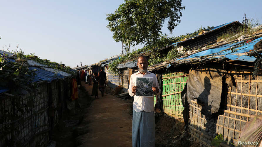 FILE - Noor Islam, from Taung Bazar village in Buthidaung township, poses for a picture with a satellite image of his burnt village in Myanmar, at the Kutupalong camp in Cox's Bazar, Bangladesh, October 15, 2018.