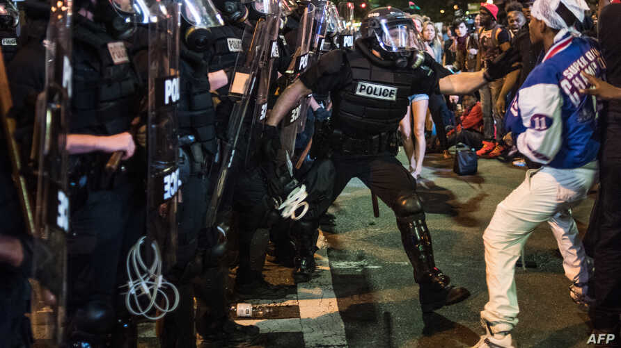 A police officer tries to grab a demonstrator during protests September 21, 2016 in downtown Charlotte, NC.
