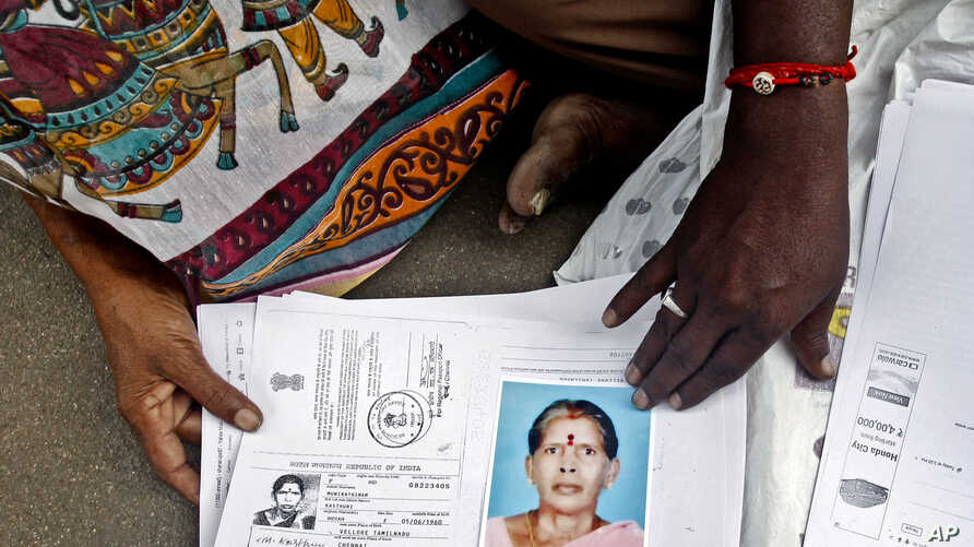 Relatives of Kasthuri Munirathinam display a photo of her and copies of her employment documents, in Chennai, India, Oct. 24, 2015.
