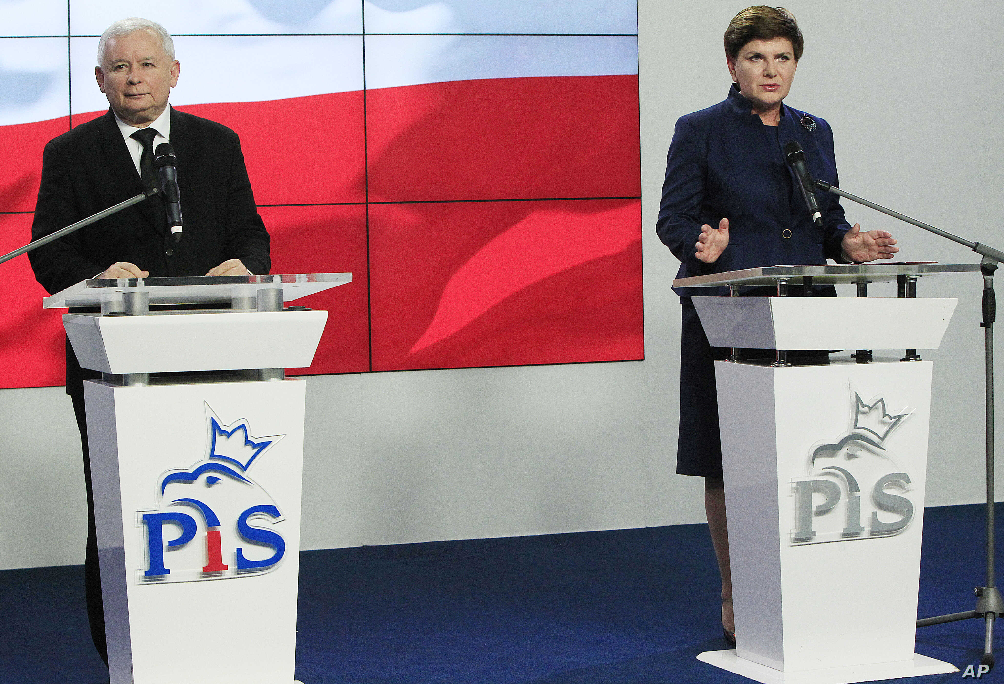 Leader of Poland's conservative Law and Justice party Jaroslaw Kaczynski, left, listens, as candidate for the prime minister's post Beata Szydlo announces names for the new government in Warsaw, Poland, Nov. 9, 2015.