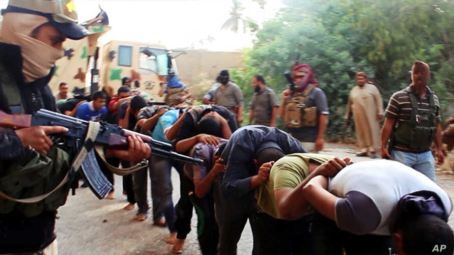 FILE - This file image posted on a militant website on June 14, 2014 which has been verified and is consistent with other AP reporting, appears to show militants from the al-Qaida-inspired Islamic State of Iraq and the Levant (ISIL) leading away capt
