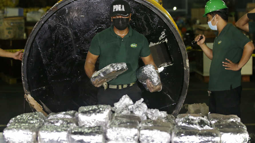 "A member of the Philippine Drug Enforcement Agency, PDEA, collects packs of Methamphetamine Hydrochloride also known as ""Shabu"" which they found hidden inside a steel cylinder in one of the biggest drug hauls in Manila, Philippines, on Aug. 7, 2018."