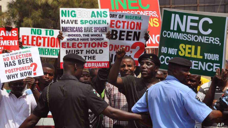 Police provide security as people demonstrate in Abuja, Nigeria, against the postponement of Nigerian elections, Feb. 7, 2015.